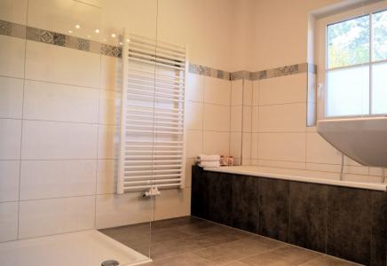 Unser geräumiges Bad mit Badewanne und Dusche.