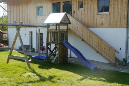 A climbing frame and swings are available for shared use.